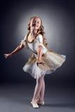 摆在微笑的小的芭蕾舞女演员看照相机 免版税库存图片
