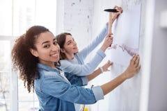 摆在快乐的女孩,当帮助挂图片时 免版税图库摄影