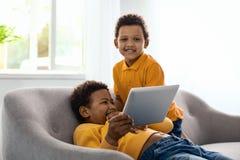 摆在快乐的小男孩,当观看与兄弟时的动画片 库存照片
