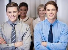 摆在快乐的工作的队,横渡的胳膊。 免版税库存照片