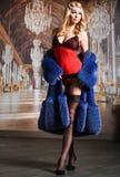 摆在性感的女用贴身内衣裤、长袜和皮大衣的曲线美美丽的妇女 免版税图库摄影