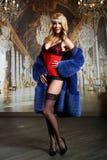 摆在性感的女用贴身内衣裤、长袜和皮大衣的曲线美美丽的妇女 免版税库存照片