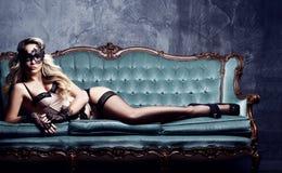 摆在性感的女用贴身内衣裤和威尼斯式m的美丽和少妇 免版税库存图片