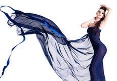 摆在性感的妇女年轻人的蓝色薄绢 图库摄影