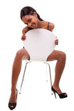 摆在性感的妇女年轻人的黑色椅子 免版税图库摄影