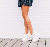 年轻摆在性感的样式室外近的红色墙壁的时尚室外女孩 自由copyspace 时髦白色运动鞋 免版税库存图片