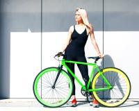 摆在性感的黑成套装备的美丽的白肤金发的女孩在一个夏日的灰色墙壁与一辆固定的绿色自行车的 库存照片