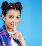 摆在情感愉快微笑在蓝色背景,生活方式人概念的年轻人相当少年现代行家女孩 免版税库存图片