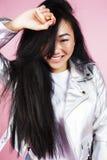 摆在情感的年轻人相当时髦的行家亚裔女孩隔绝在桃红色背景愉快的微笑的凉快的微笑,生活方式 库存图片