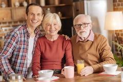 摆在愉快的家庭,当食用早餐在厨房时 免版税库存图片