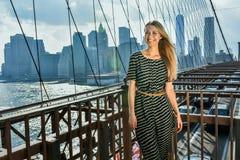摆在愉快的美丽的女孩,当站立在一座河桥梁在一个夏天晴天时 免版税库存照片