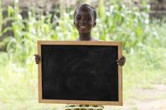 摆在户外与黑板的非洲女孩 库存照片