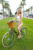摆在户外为与减速火箭的自行车的照相机的时髦的衣裳的可爱的女性行家 图库摄影