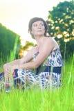 摆在户外在日落的美丽的作的松弛白种人深色的妇女画象反对森林背景 库存照片