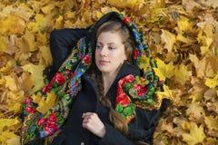 摆在户外在秋天公园的年轻美丽的深色的妇女 免版税图库摄影