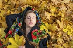 摆在户外在秋天公园的年轻美丽的深色的妇女 免版税库存照片