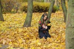 摆在户外在秋天公园的年轻美丽的深色的妇女 图库摄影