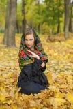 摆在户外在秋天公园的年轻美丽的深色的妇女 免版税库存图片