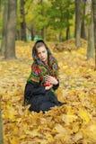 摆在户外在秋天公园的年轻美丽的深色的妇女 库存照片