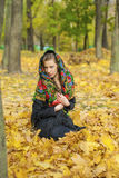 摆在户外在秋天公园的年轻美丽的深色的妇女 库存图片