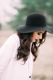 摆在户外在门附近的一件黑帽会议和白色外套的美丽的时兴的微笑的妇女 库存照片