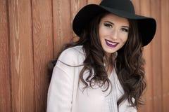 摆在户外在门附近的一件黑帽会议和白色外套的美丽的时兴的微笑的妇女 库存图片
