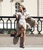摆在户外在晴朗的wea的米黄外套的年轻美丽的妇女 免版税库存图片