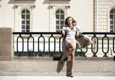 摆在户外在晴朗的wea的米黄外套的年轻美丽的妇女 图库摄影