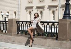 摆在户外在晴朗的wea的米黄外套的年轻美丽的妇女 免版税库存照片