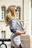 摆在户外在su的米黄短的礼服的年轻美丽的妇女 免版税库存图片