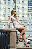 摆在户外在su的米黄短的礼服的年轻美丽的妇女 库存图片