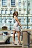 摆在户外在su的米黄短的礼服的年轻美丽的妇女 免版税库存照片
