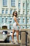 摆在户外在su的米黄短的礼服的年轻美丽的妇女 免版税图库摄影