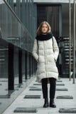 摆在户外春天秋天的年轻美丽的白肤金发的时髦的女孩全长城市画象在白色外套黑色编织了围巾 免版税库存照片