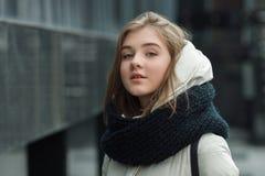 摆在户外春天秋天的年轻美丽的白肤金发的时髦的女孩城市画象在白色外套黑色编织了围巾 葡萄酒fil 免版税库存图片