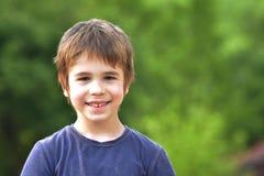 摆在户外本质上的逗人喜爱的微笑的小男孩 库存照片