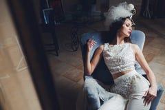 摆在扶手椅子的时髦的新娘 库存图片