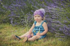 摆在接近lavander灌木佩带的牛仔裤的中央公园草甸的年轻秀丽儿童女孩穿戴和与我的紫罗兰色紫色班丹纳花绸 免版税库存照片