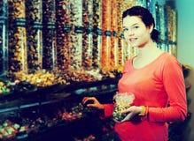 摆在摄影师的妇女采摘不同的糖果 免版税库存图片