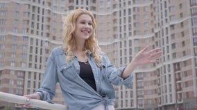 摆在摩天大楼前面的牛仔裤夹克的画象逗人喜爱的确信的白肤金发的妇女,看微笑 城市生活方式 股票视频