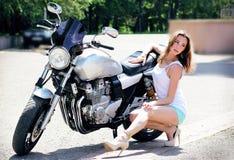 摆在摩托车附近的短的短裤的女孩 免版税库存图片