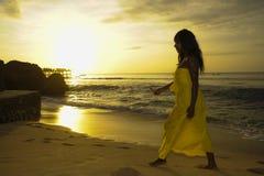 摆在放松的走在夏天日落海滩的别致和典雅的夏天礼服的迷人的非裔美国人的黑人妇女 库存照片