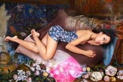 摆在放松的说谎在黑背景的辎重袋的一件花卉蓝色礼服的迷人的妇女 免版税库存图片