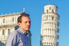 摆在斜塔前面的一个白年轻人在比萨 免版税库存照片