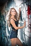 摆在方式的白肤金发的女孩在街道画墙壁附近 库存图片