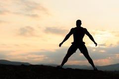 摆在日出或日落的爱好健美者剪影在山 显示他的肌肉的英俊的大力士 图库摄影