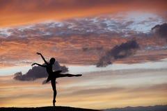 摆在日落期间的跳芭蕾舞者 免版税库存图片