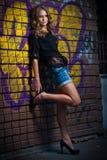 摆在时尚的秀丽女孩在街道上的红砖墙壁附近 免版税库存照片