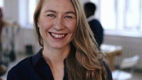 摆在时髦现代办公室工作场所的愉快的白种人白肤金发的女商人特写镜头画象,快乐地微笑 股票视频
