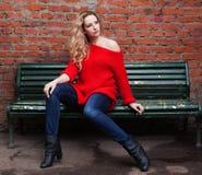 摆在时髦红色毛线衣、牛仔裤和黑起动的一个难以置信的白肤金发的女孩坐长凳对砖墙 库存照片